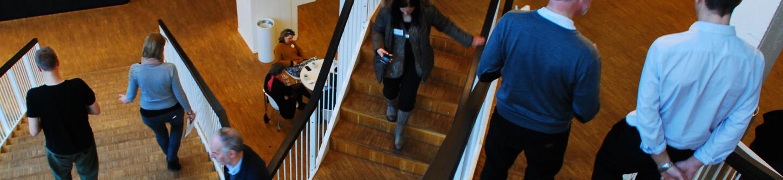 Kursusdeltagere på vej ned af trapperne under kursus på Porcelænshaven 22, Frederiksberg