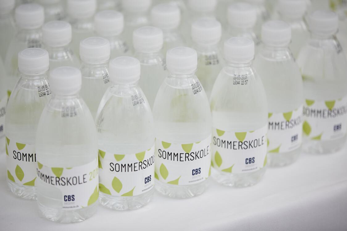 Baggrundsbillede med vandflasker med Sommerskole-logo