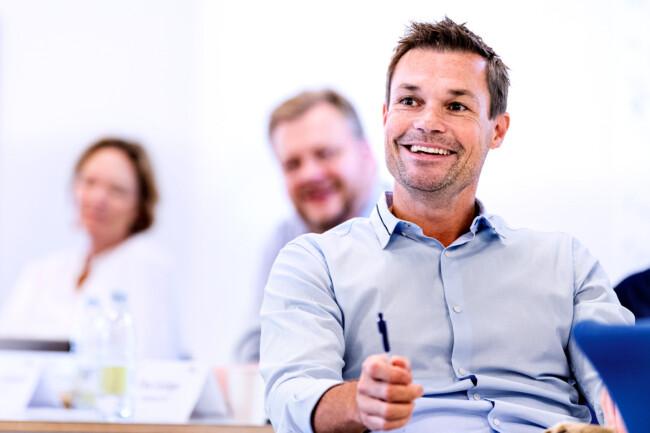 Billede af glade og underholdte deltagere ved kursus hos CBS Executive